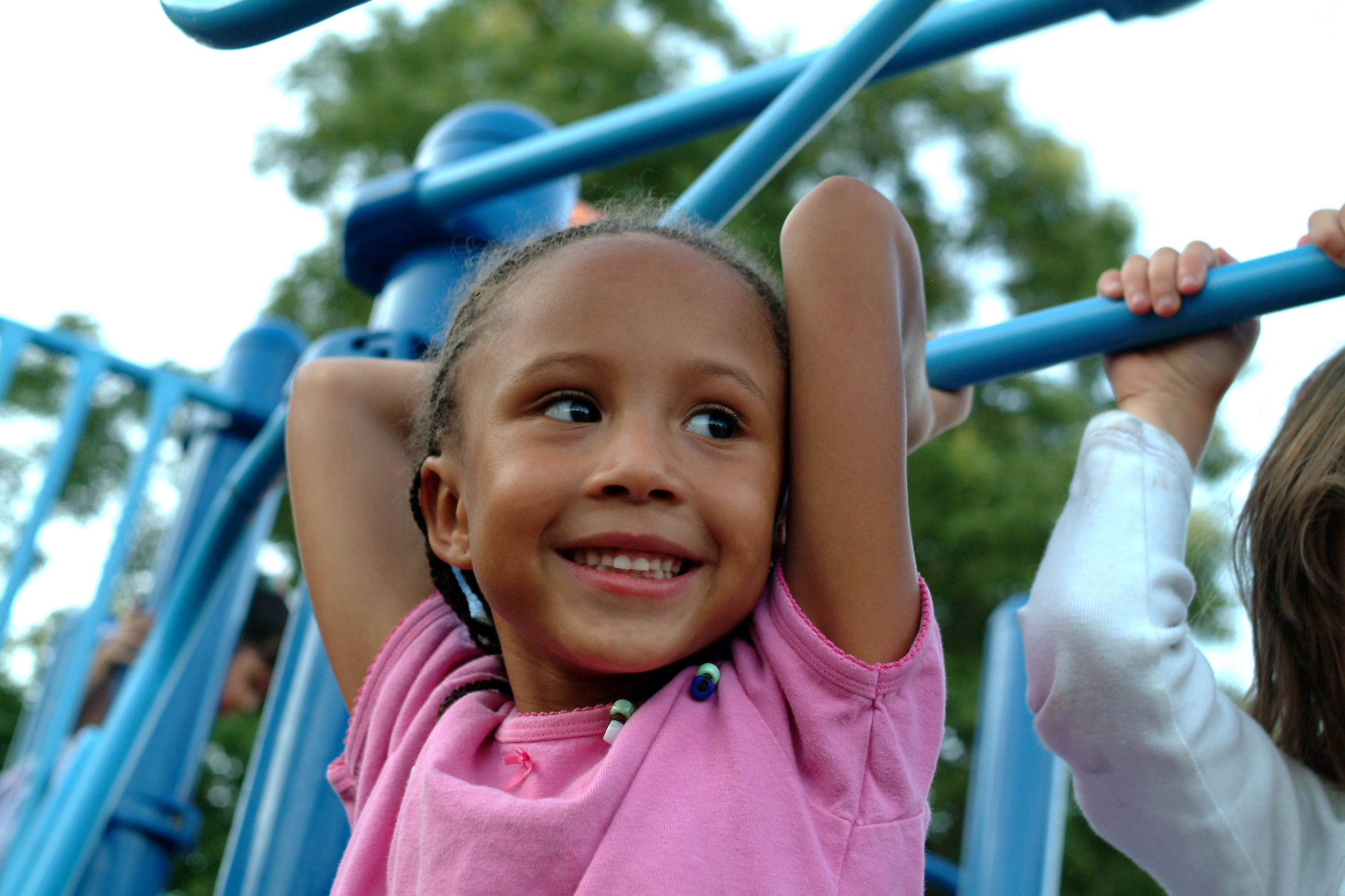 Young African American girl swings from jungle gym