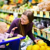Woman with baby selects healthy food at grocery store