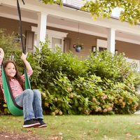 Father and daughter swing outside house