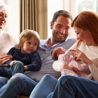 Multigenerational family gathers around newborn baby
