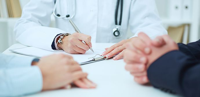 Physician sits with two patients filling out paperwork